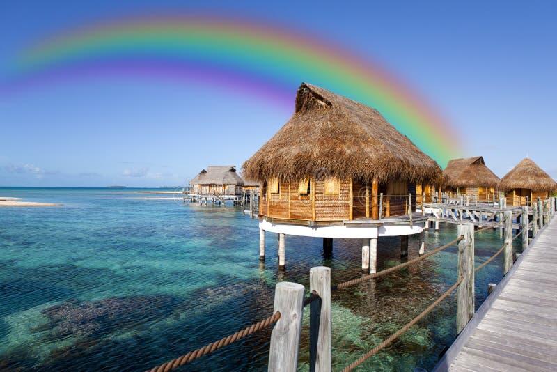 Cabanas sobre o mar e um arco-íris sobre eles imagens de stock royalty free
