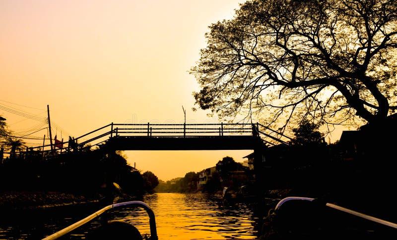Cabane dans un arbre de pont de tour de bateau de soirée de silhouette le long de canal photos stock