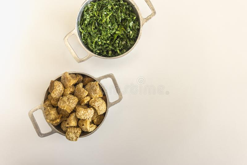Cabbage and crackling accompanies the feijoada, Brazilian typical dish stock photography