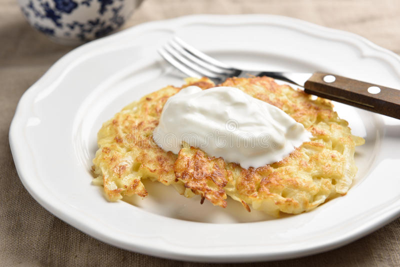 Cabbage patties with sour cream on a plate stock images