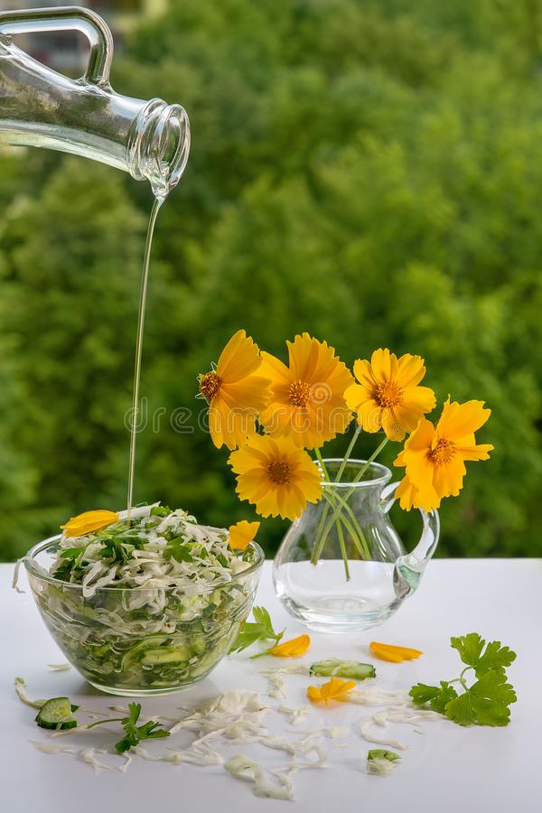 Cabbage salad and a bouquet of yellow flowers. On the white table with Green blurred background. Poured oil from the bottle into a bowl of salad. Plenty of stock image