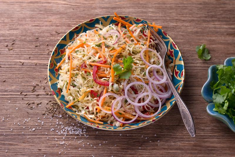 Cabbage salad with carrots, red pepper, onions, cilantro and spices royalty free stock image