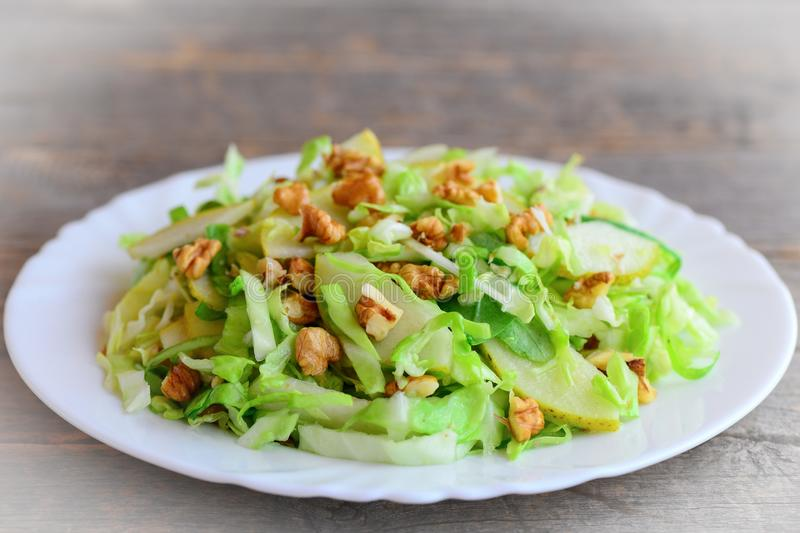 Cabbage slaw with pear and walnuts. Quick pear and cabbage slaw on a plate. Vitamin rich food. Vegetable salad cold. Summer salad. Summer vegetable salad recipe royalty free stock photography