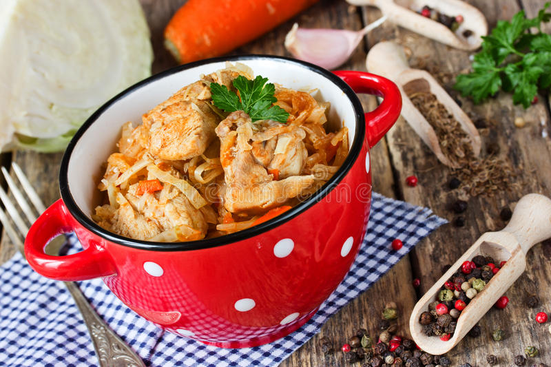 Cabbage stew with meat on red bowl with dots, hearty rustic dish stock photos