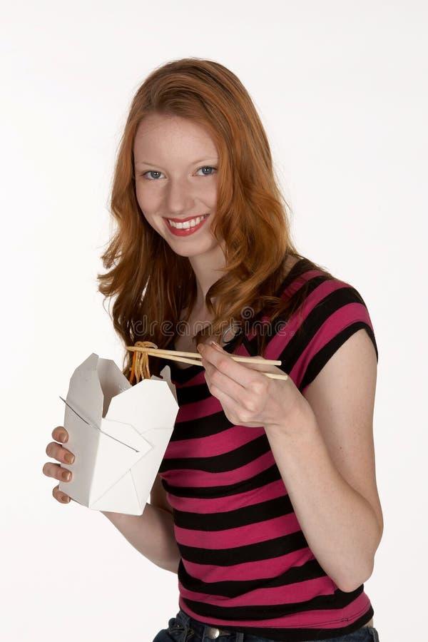 Cabeça consideravelmente vermelha que come macarronetes chineses foto de stock