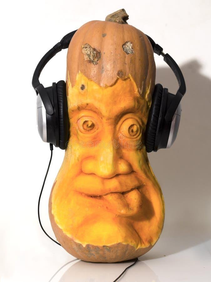 Cabeça da abóbora de Haloween esculpida com fones de ouvido foto de stock royalty free
