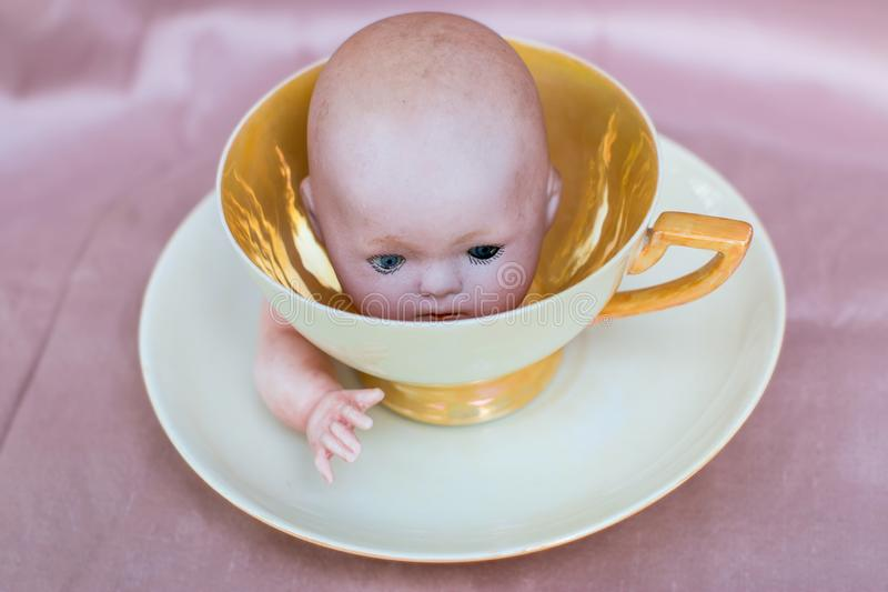 Cabeça da boneca do vintage dentro do copo antigo do café ou de chá com os pires - assustadores e surreais imagem de stock royalty free
