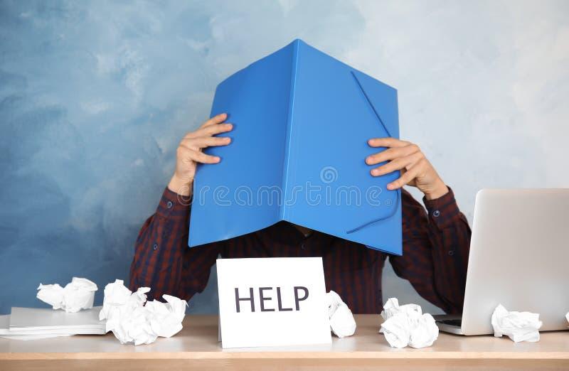 Cabeça da coberta do homem com o dobrador na tabela no escritório fotos de stock