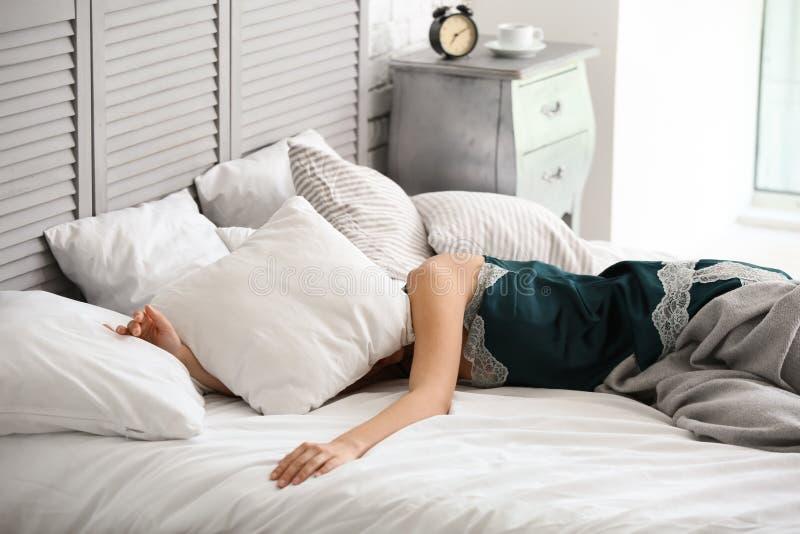 Cabeça da coberta da jovem mulher com descanso ao tentar dormir na cama fotografia de stock royalty free