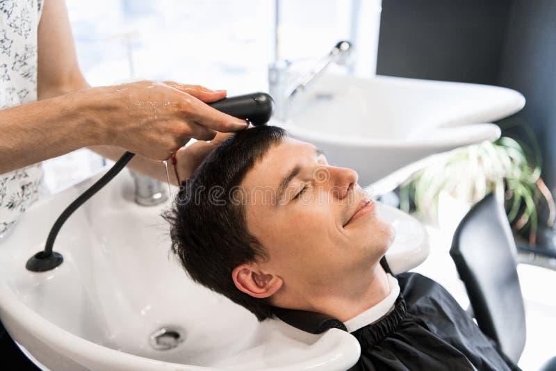 Cabeça da lavagem do cabeleireiro do homem de um cliente de sorriso considerável imagens de stock royalty free