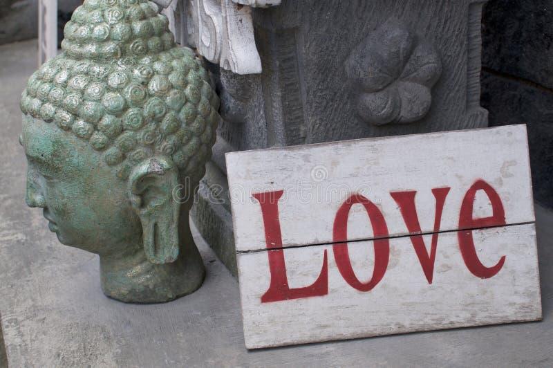 Cabeça de buddha da pedra com um sinal de madeira do amor foto de stock royalty free