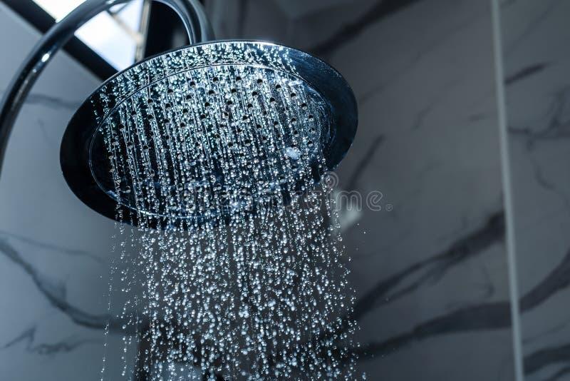 [cabeça de chuveiro da cabeça de chuveiro] no banheiro com fluxo das gotas da água fotos de stock royalty free