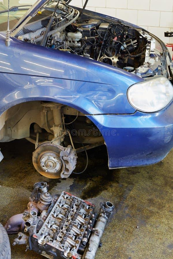 A cabeça de cilindro do motor encontra-se no assoalho perto do carro foto de stock