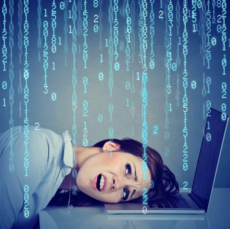 Cabeça de descanso forçada desesperada da mulher no portátil com o código binário que cai para baixo imagem de stock royalty free