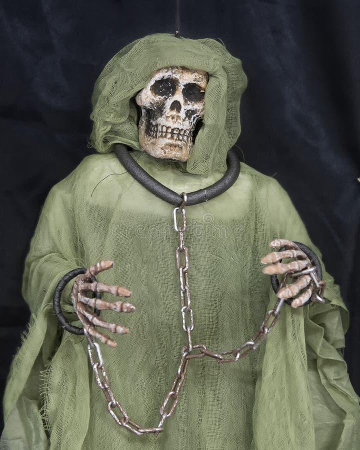 Cabeça de esqueleto e mãos do monstro acorrentadas junto fotos de stock