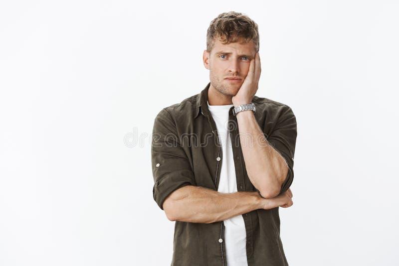 Cabeça de inclinação impossível e afligida virada do noivo considerável louro cansado na palma que olha a câmera com desesp fotografia de stock royalty free