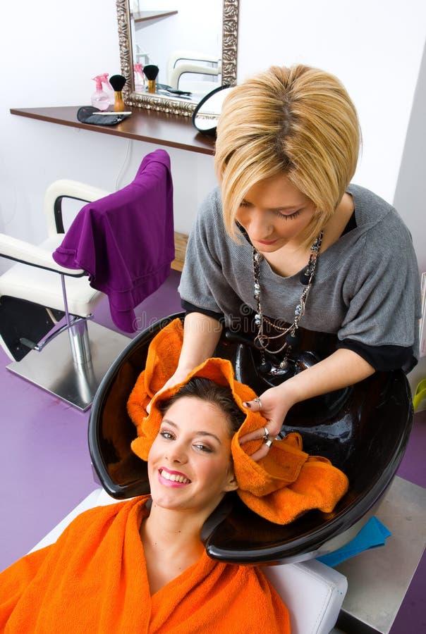 Cabeça de lavagem da mulher do estilista de cabelo foto de stock