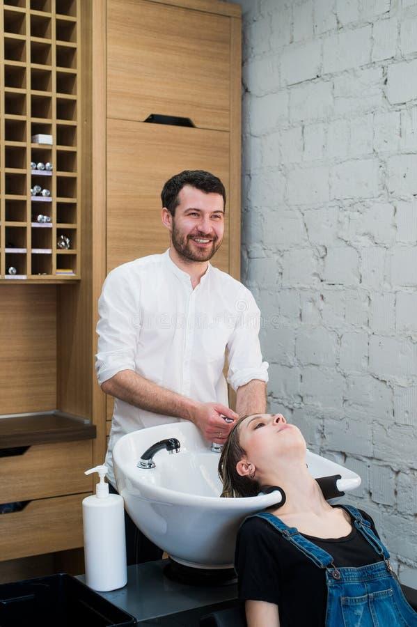 Cabeça de lavagem do barbeiro à jovem mulher no cabeleireiro imagens de stock