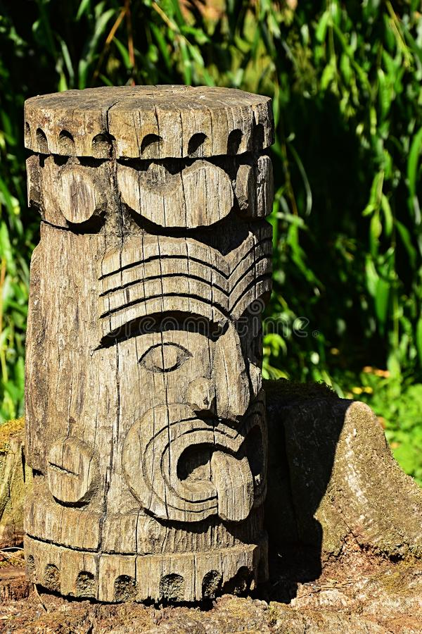 Cabeça de madeira ou totem do nativo americano decorativo, propably asteca ou maia, indicado no suporte de pedra foto de stock