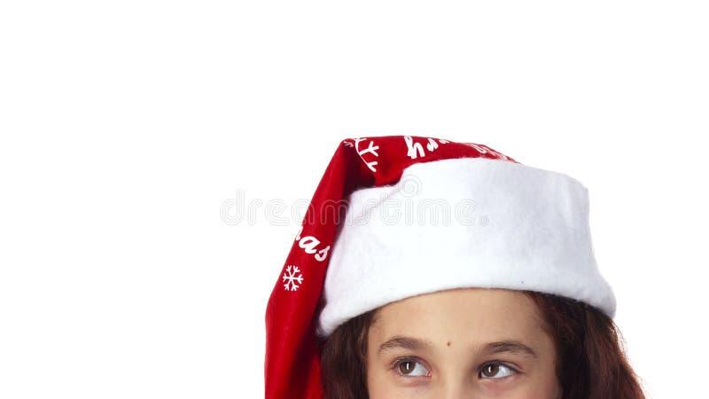 A cabeça de uma menina vestida em um chapéu de Santa Claus é mostrada perto acima imagem de stock