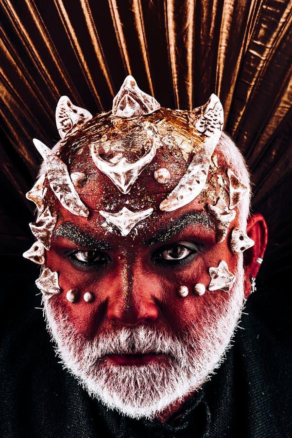 Cabeça do demônio com os espinhos na cara que aparece da escuridão, conceito do submundo Monstro mau com vestir vermelho da pele  foto de stock