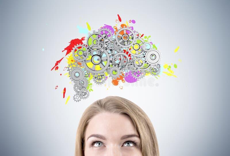 Cabeça e cérebro louros da mulher s com engrenagens foto de stock