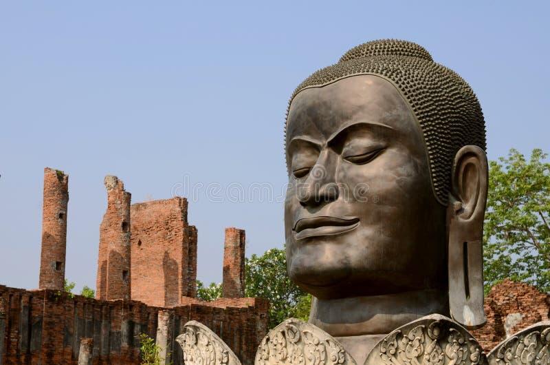 Cabeça grande da Buda com o polo velho vermelho do tijolo no fundo, céu azul imagem de stock