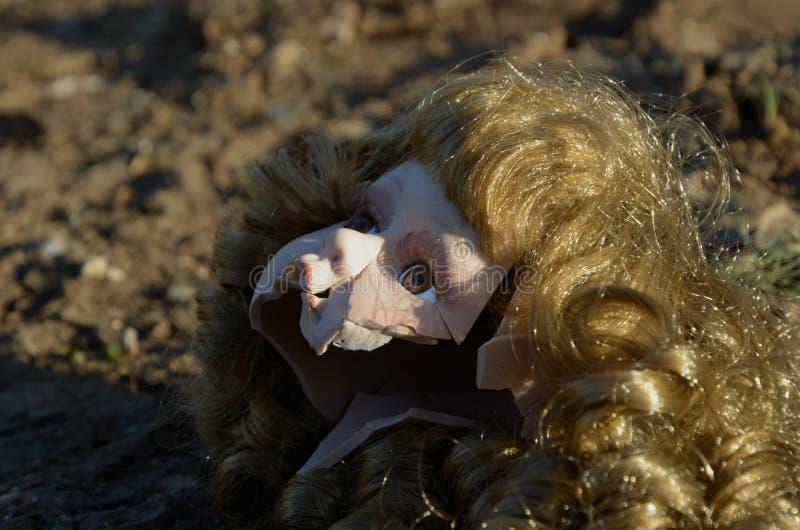 Cabeça quebrada da boneca na terra foto de stock royalty free