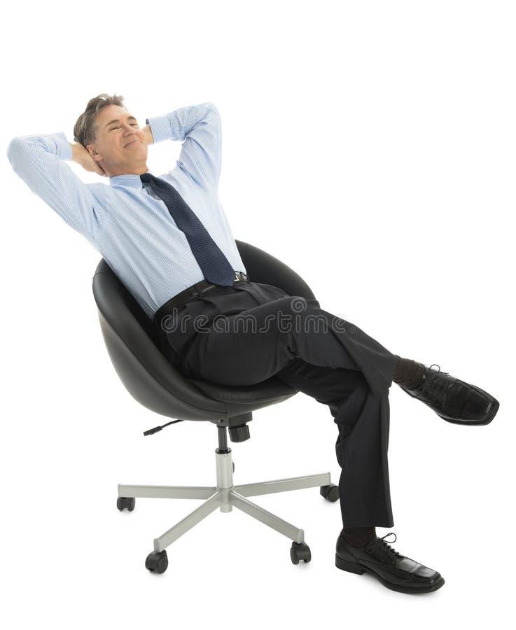 Cabeça relaxado de With Hands Behind do homem de negócios que senta-se no escritório Cha imagem de stock