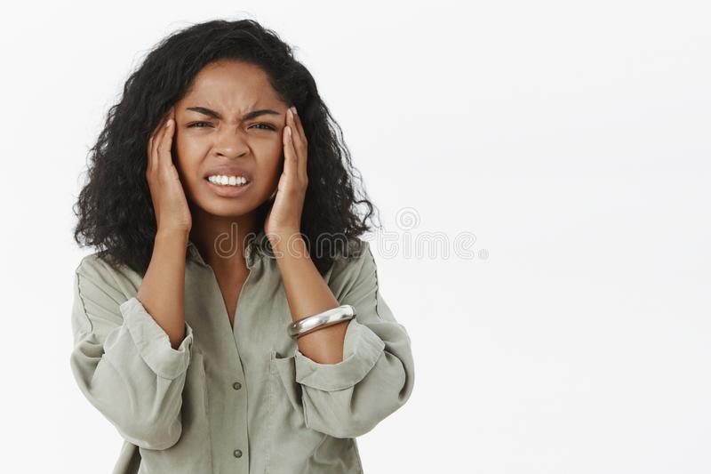 A cabeça vai circularmente da manutenção Retrato da jovem mulher afro-americano intensa desagradada com cabelo encaracolado que o fotografia de stock