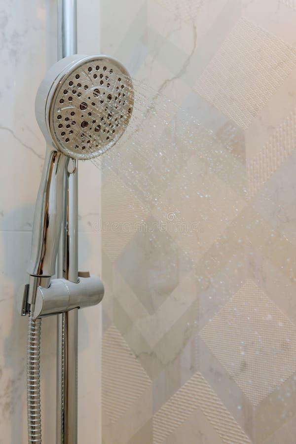 A cabe?a de chuveiro com ?gua deixa cair a queda em um banheiro fotografia de stock royalty free
