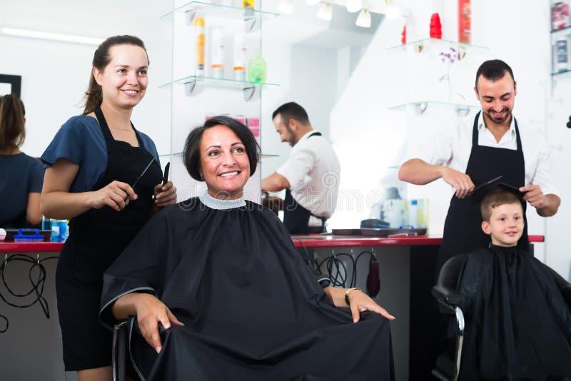 Cabeleireiro alegre da mulher que corta o cliente fêmea fotos de stock