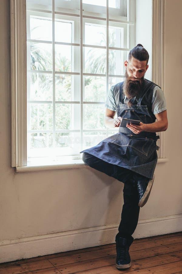 Cabeleireiro com a tabuleta digital em seu salão de beleza imagens de stock royalty free