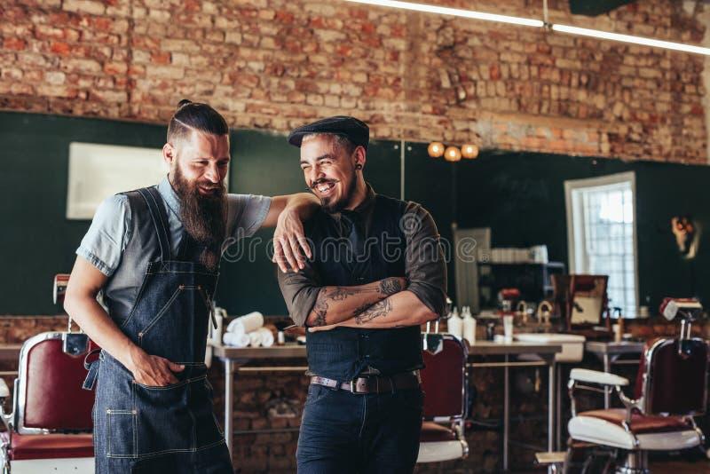 Cabeleireiro com um homem que está no barbeiro fotografia de stock