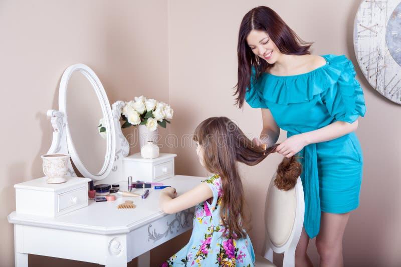 Cabeleireiro da mãe sua filha bonita do preteen em casa fotos de stock