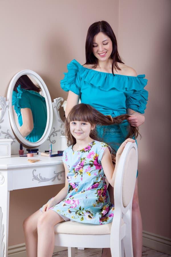 Cabeleireiro da mãe sua filha bonita do preteen em casa imagens de stock