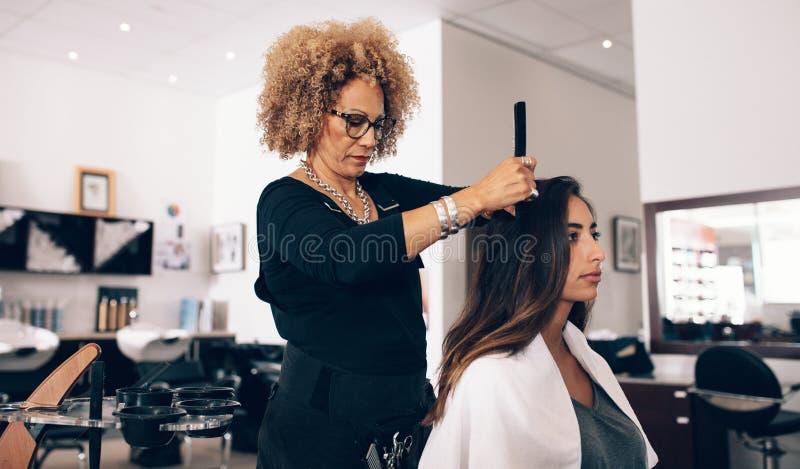 Cabeleireiro da mulher no trabalho no salão de beleza fotografia de stock
