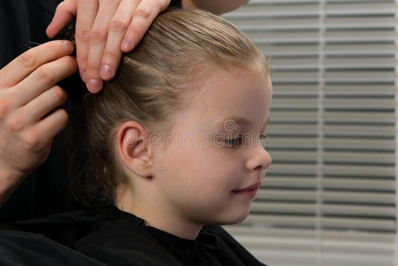 Cabeleireiro do estilista cria um penteado para a noite, menina, cabelo com um gancho de cabelo, sorrisos das facadas do bebê imagem de stock royalty free