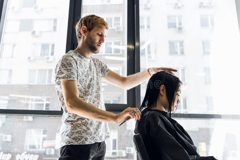 Cabeleireiro e cliente de sorriso do cabeleireiro em um salão de beleza ao fazer um corte de cabelo novo à mulher moreno bonita fotos de stock