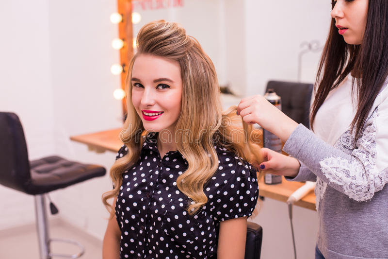 Cabeleireiro fêmea que está e que faz o penteado à jovem mulher bonita bonito foto de stock royalty free