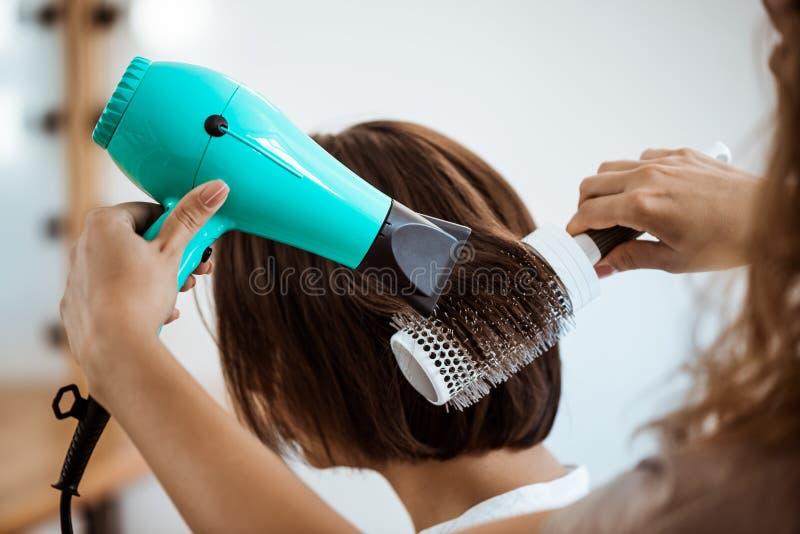 Cabeleireiro fêmea que faz o penteado à menina moreno no salão de beleza foto de stock