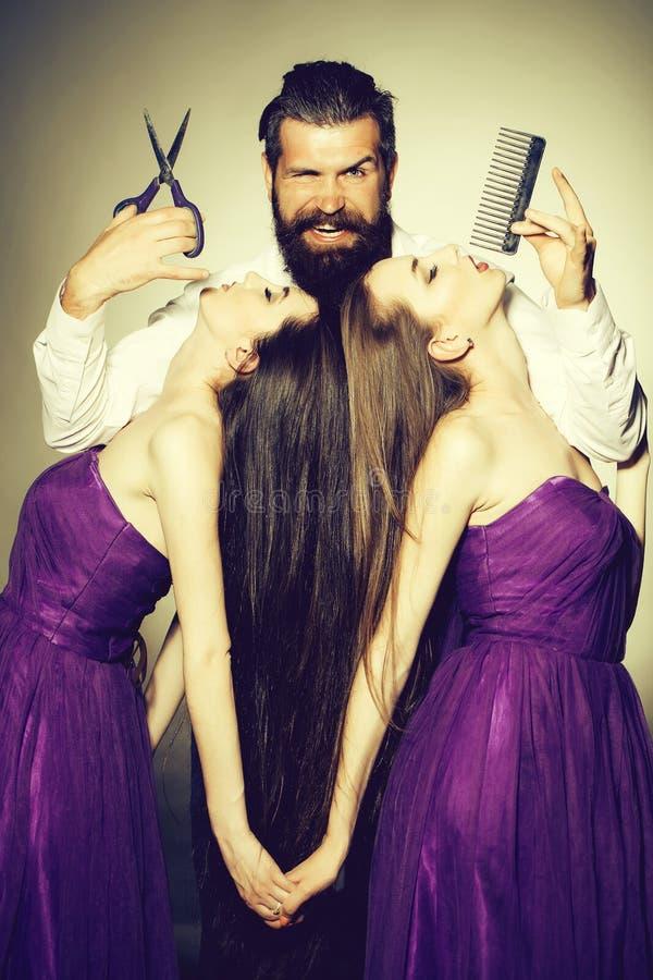 Cabeleireiro farpado do homem e duas mulheres foto de stock