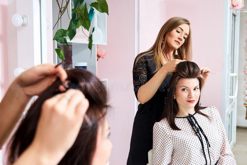 cabeleireiro no trabalho - o cabeleireiro faz o cabelo de uma morena nova bonita ao cliente no salão de beleza imagens de stock royalty free