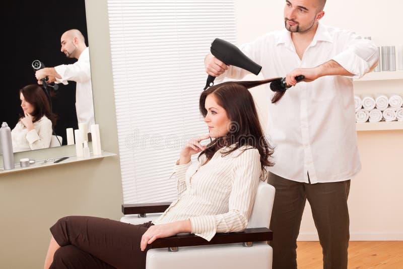 Cabeleireiro profissional com o secador de cabelo no salão de beleza imagens de stock royalty free