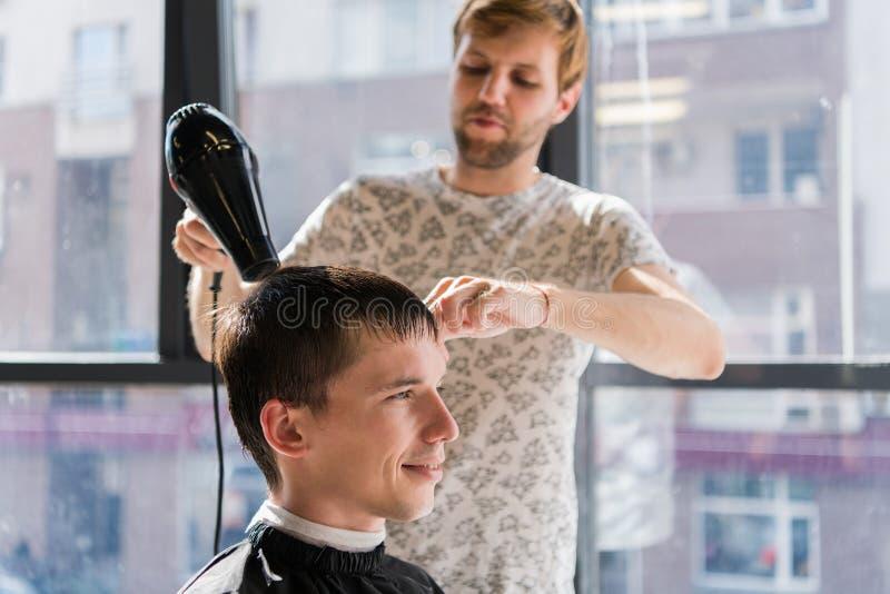 Cabeleireiro profissional Disparado de um cabelo de secagem do cabeleireiro com o secador do sopro do cliente do homem fotografia de stock