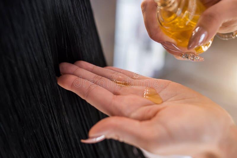 Cabeleireiro que aplica a máscara do óleo ao cabelo Skincare e haircare imagens de stock