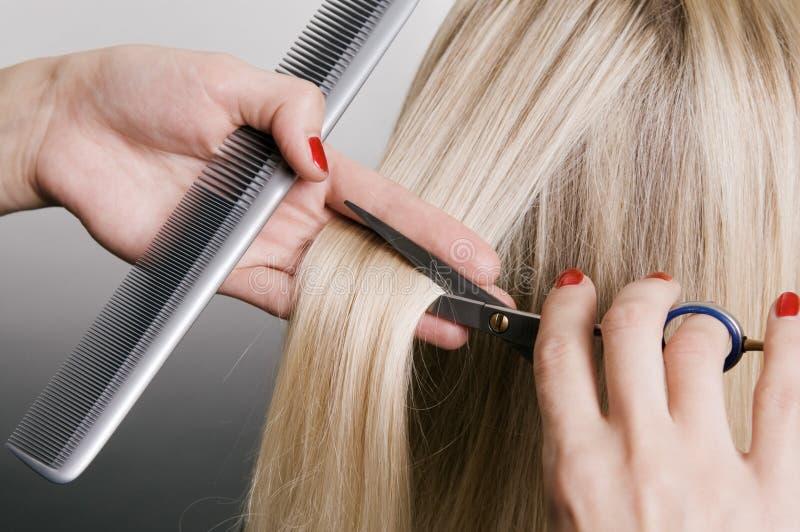 Cabeleireiro que corta o cabelo louro fotografia de stock