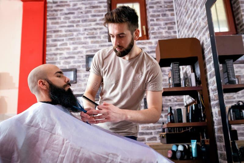 Cabeleireiro que corta uma barba do ` s do cliente com tesouras imagens de stock