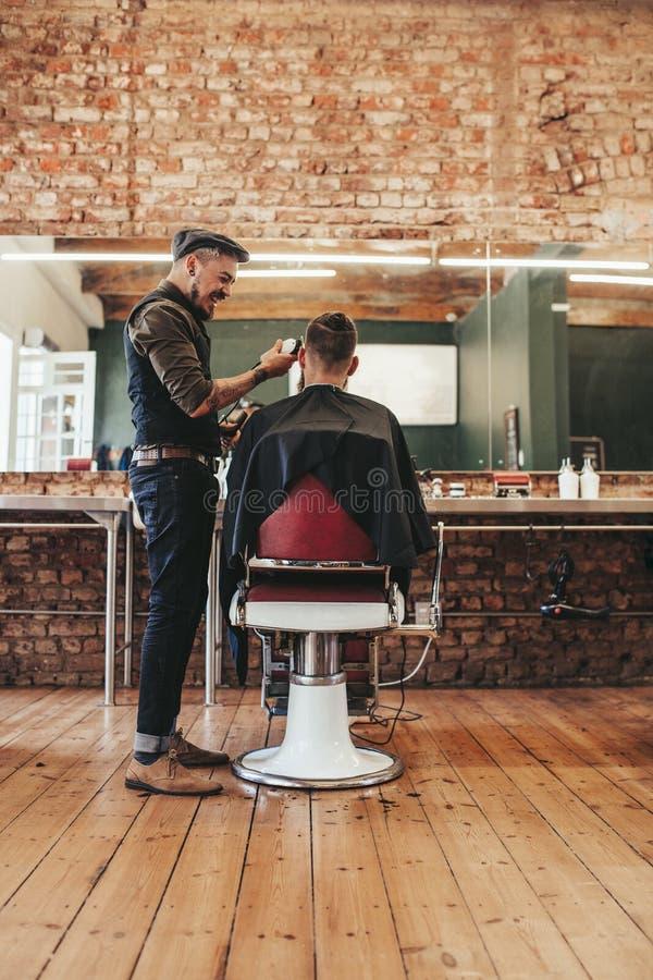 Cabeleireiro que dá o corte de cabelo ao cliente no salão de beleza imagem de stock royalty free
