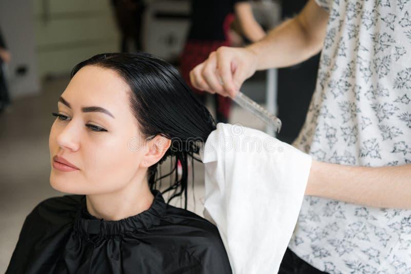 Cabeleireiro que envolve a toalha na cabeça do ` s do cliente Mulher moreno que obtém o tratamento do cabelo em um salão de belez imagem de stock